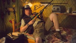 Tobias poserar med ett vapen på sin säng.