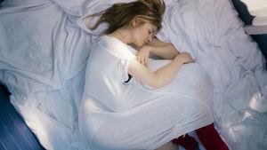 Astrid ligger och håller om sin dotter Nele som krupit in under hennes nattlinne.