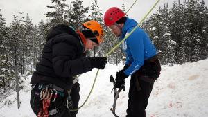 Heidi Pienipaavola ohjeistaa kuinka jääkiipeilyyvarusteet toimivat.