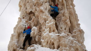 Miehet kiipeävät 21 metriä korkeaa jäätornia Oulussa.