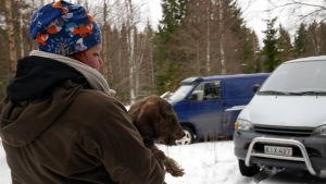 Riikka Simola kantaa mäyräkoiraa autoon metsästyreissulla.