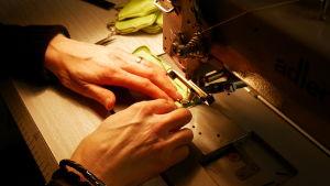Kädet ompelukoneella ompelemassa.