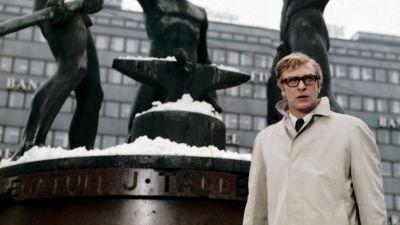 Michael Caine seisoo Kolmen sepän patsaan edessä. Kuva elokuvasta Miljardin dolalrin aivot.
