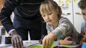 Lastenhoitaja ja Ines Jokela pelaavat koodauspeliä.