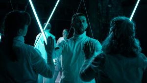 Scenkonstnärer i vitt står mot en mörk fond som lyses upp av blåskiftande lysrör.