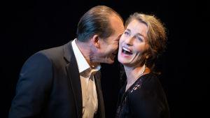 En man lägger sitt ansikte mot en kvinnas hals, hon vänder ansiktet upp och skrattar.