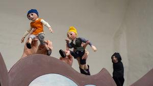 I pjäsen ingår olika dockor. På bilden syns tre dockor, varav de två första klädda i färgglada plagg och den tredje i en mörk kåpa.