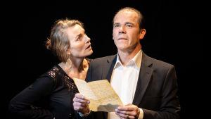 En man håller ett brev i handen och stirrar ut i luften framför sig. En kvinna bredvid honon ser bestört på honom.