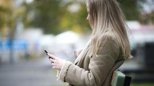 Ung kvinna sitter på en bänk med mobiltelefon i handen,