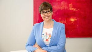 Kvinna med kort hår och glasögon ler mot kameran. I bakgrunden en röd tavla.