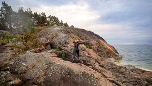 En person i våtdräkt springer upp för klippstrand.