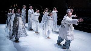 Ett dussin skådespelare i vitt står i en kilformad grupp och pekar med hela armen åt samma håll mot höger om kameran.
