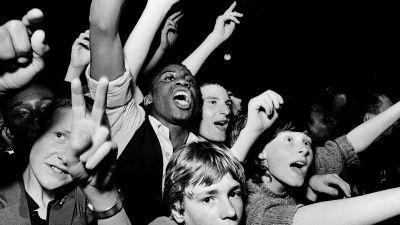 Rock-konsertin yleisöä lähikuvassa. 1978 Lontoo, kuva dokumenttielokuvasta White Riot.