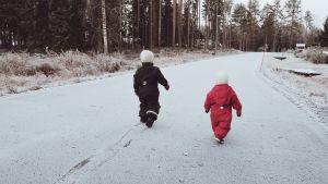 Barn som går på en snöig väg.
