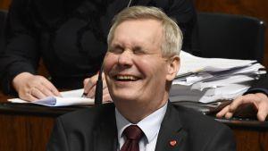 Antti Rinne skrattar gott i plenisalen i riksdagen den 8.3.2019.