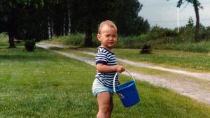 Tim Sparv som barn med blått ämbar i handen på gräsmatte vid sandstig.