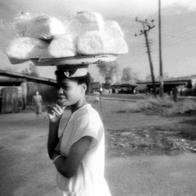 Etelä-Afrikkalainen tyttö kantaa pään päällä tarjotinta täynnä leipiä