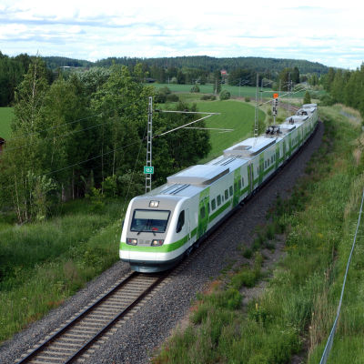 Ett passagerar tåg i vita och gröna färger kör fram i en svag kurva genom ett grönt och lummigt landskap. Järnvägen har bara ett spår.