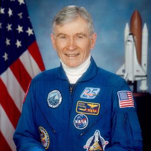 John Young i mogen ålder poserar framför USA:s flagga och ett modellrymdskepp.