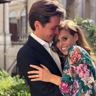 En kostymkläddman kramar om en kvinna i blommig klänning. Kvinnan håller fram sin hand där man kan se hennes stora föärlovningsring.