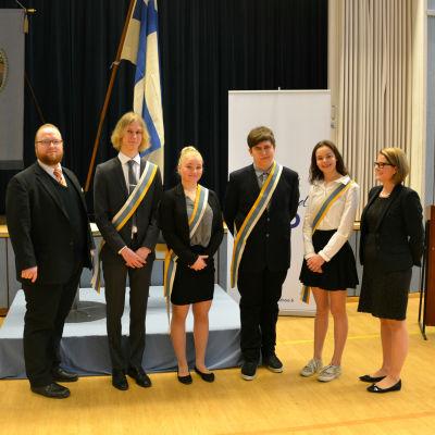 Sex finklädda personer står på rad. I bakgrunden syns Finlands flagga.