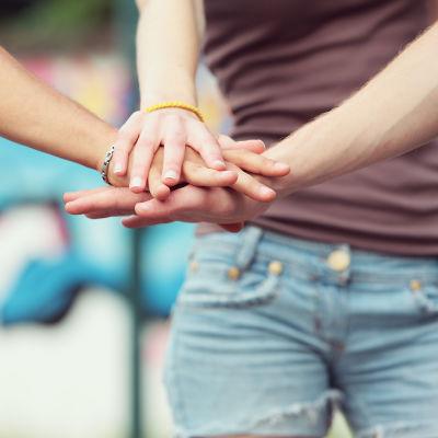 Händer på varandra, i bakgrunden en person med jeans och en graffitimålning.
