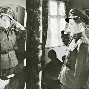 Alokas (Lasse Pöysti) peilailee kenraalin lakki päässään.