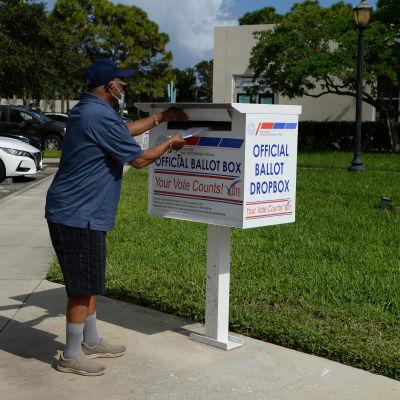 Mies pudottaa ennakkoäänestyslipukkeen laatikkoon Palm Beachissä, Floridassa..