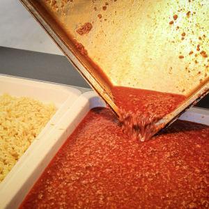 Pasta med köttfärssås i stora kärl.