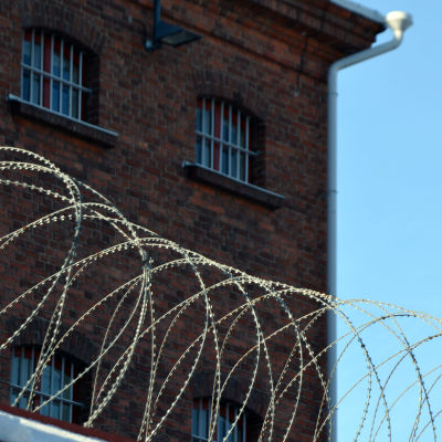 Vankilan seinää ja piikkilanka-aitaa