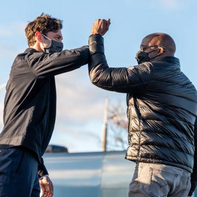 Två män hälsar på varandra med armarna i luften. De bär båda munskydd och svarta jackor.
