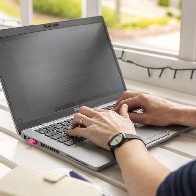 Kirsi Vehkakoski kirjoittaa tietokoneella kotinsa parvekkkeella.