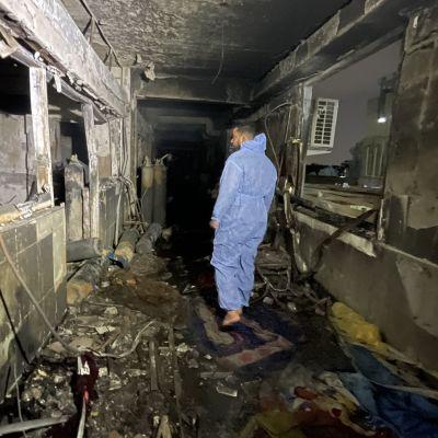 En man i skyddsdräkt går i en sjukhuskorridor som förstörts till följd av en brand.