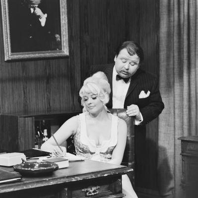 """Kuva mustavalkoisesta tv-ohjelmasta """"Akkavalta - Woman power"""" vuodelta 1969. Kuvassa johtajaa näyttelevä Jukka Sipilä ja sihteerinä Sirpa Fransman."""