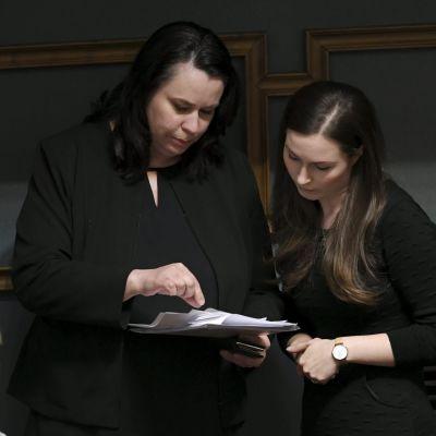 Två kvinnor klädda i svart ser på ett papper som den ena kvinnan har i handen.