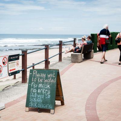 Två personer går på en strandpromenad, i bakgrunden syns oceanen.