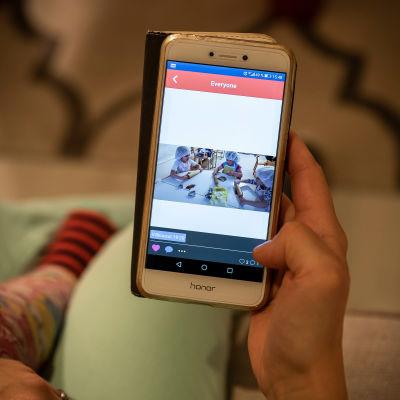Käsi pitelee älypuhelinta, jonka ruudulla kuva päiväkotilapsista leipomassa.