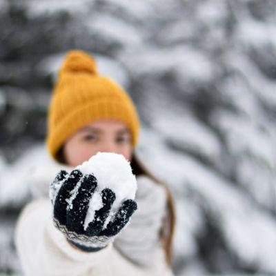 Flicka håller i en snöboll