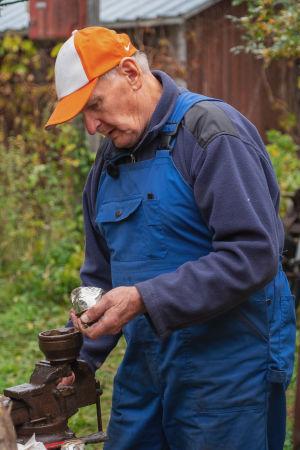 Lippalakkipäinen mies tekee vanhasta juomatölkistä silmää Villasarvikuono-veistokselle.
