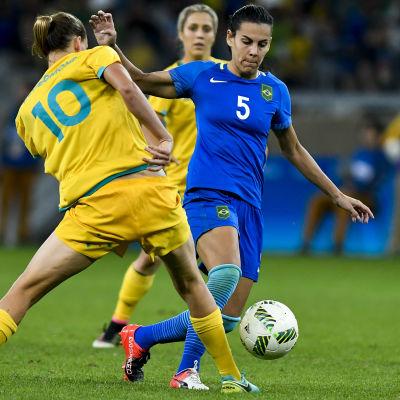 Damfotbollspelare iklädd blått fintar förbi motståndare.