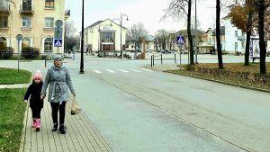 En liten flicka går med sin far- eller mormor på stadens gator i Kohtla-Järve i Estland.