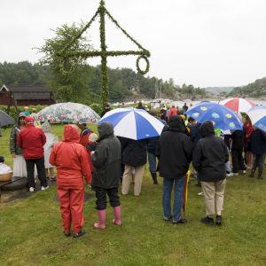 människor i regnmundering runt en midsommarstång.