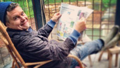 Owe Salmela sitter i korgstol och läser tidning