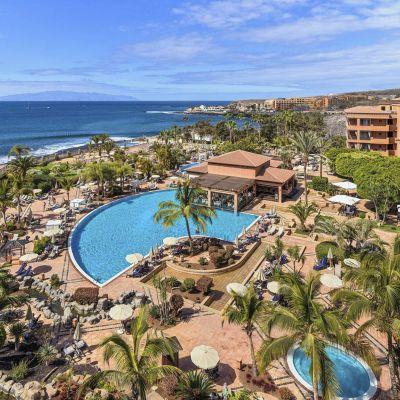 Ett hotell med terracottabruna väggar, en pool och palmer.