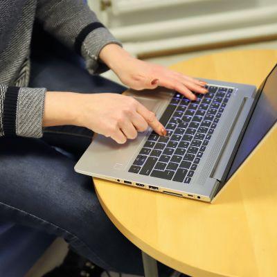 Nainen kirjoittaa kannettavalla tietokoneella.