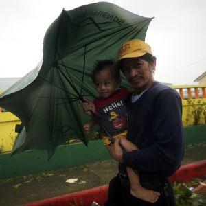 En man och hans barn i den tyfondrabbade byn Aparri i provinsen Cagayan i Filippinerna.