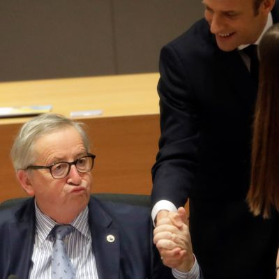 Macron puristaa Junckeria kädestä