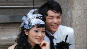 Ett brudpar från Hongkong blir fotograferade. Bruden har en stor, vit fjäderprydnad i sitt hår.