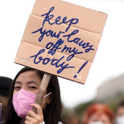 """Collage med två bilder. Till vänster en kvinna som håller upp en skylt där det står """"Håll tassarna borta från min kropp"""". Till höger en kvinna som håller i en proptyp av ett litet foster."""