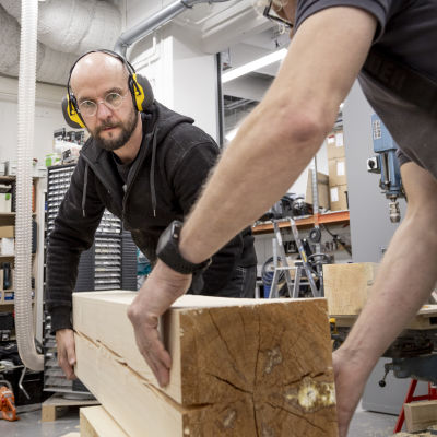 Näyttelyrakentaja nostaa puupalkkia.